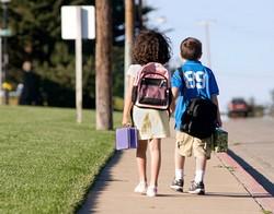 Девочка и мальчик идут держась за руки с рюкзаками