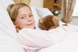 Девочка улабается, девочка в кровати с мягкой игрушкой медведем
