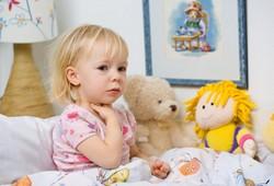 Девочка сидит на кровати и держится за горло. У девочки болит горло