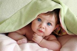 Ребенок под зеленым полотенцем с голубыми глазами