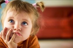 Девочка с косичками в задумчивой позе