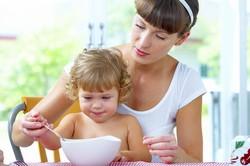 Мама кормит ребенка ложкой из тарелки