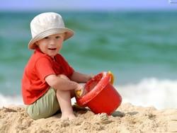 Мальчик на пляже с красным ведром в панаме