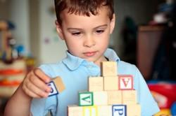 Ребенок с аутизмом собирает кубики