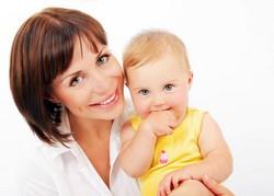 Ребенок улыбается, на руках у врача