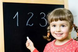 Девочка возле школьной доски и цифры