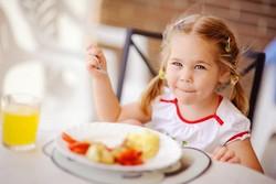 Девочка обедает за столом