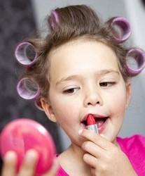 Маленькая девочка красит губы помадой в бигудях
