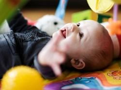 Ребенок в кроватке играется с игрушками