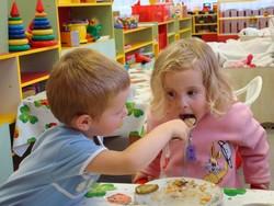 Мальчик кормит девочку в детском саду