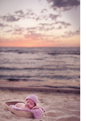Ребенок спит на пляже в корзинке